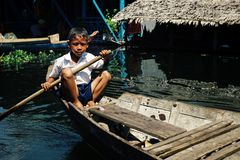 Local school boy student paddling home after class at the lake on his canoe in front of the floating stilt house settlement. Illegal community , Tonle Sap lake stock photos