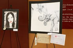 Local school hosting district art fair. Showing portrait of a young girl, a drawing of an elephant, and certificates for winners stock image