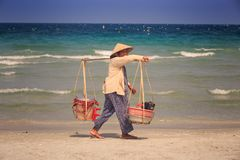 Local Seller with Goods in Baskets Walks along Ocean Beach Royalty Free Stock Images