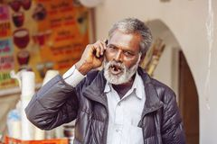 Local seller on public market speaking with his cellphone. Pushkar, Rajasthan, India, February 14, 2018: Local seller on public market speaking with his stock image