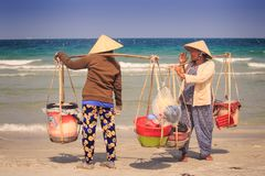 Local Sellers with Goods in Baskets Talk on Ocean Beach Stock Photography