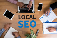 Local SEO Concep. Business team hands at work with financial reports and a laptop, top view stock photo