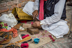 A local skilled cobbler making shoes and slippers at his shop for sale. Stock Images