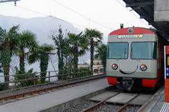 Local smiling train in Lugano, Switzerland, with palm trees and mountain silhouettes Royalty Free Stock Photos
