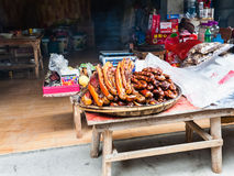 Local smoked pork products in front of eatery. CHENGYANG, CHINA - MARCH 27, 2017: local smoked pork products in front of eatery in Chengyang village of Sanjiang Stock Photos