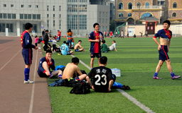 Pengzhou, China: Chinese Soccer Players. Local soccer teams taking a break from a game sitting on the Astroturf at Pengzhou stadium in Pengzhou, China Royalty Free Stock Photos