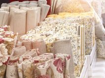 A display of a textile market with different pastel colored cloth fabrics stock photo