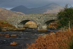 Local stone just works. A typical stone bridge - made of local stone - in the Scottish Highlands, with the imposing mountain behind Royalty Free Stock Image