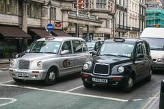 Local taxis in London. LONDON, UK - APRIL 19, 2012 : Traditional black and silver cabs are on the traffic Stock Image