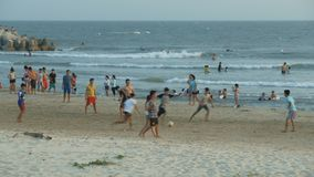 Local Teenagers Play Football on Sand by Azure Sea. MUI NE/VIETNAM - MARCH 24 2018: Local teenagers play football on wet sand beach against walking people and stock video footage