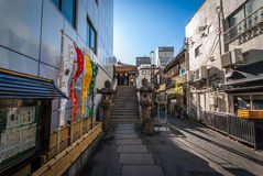 Local Temple in Tokyo. Tokyo, Japan - January 23, 2015:  A small local shrine nestled between an office building, homes and a restaurant in the Nihonbashi area Royalty Free Stock Images