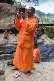 Local tourist taking photos with mobile phone at Ravana falls Royalty Free Stock Photos