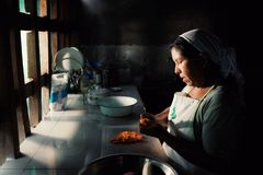 local tribal lady preparing traditional food at her rainforest home stock image