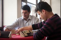 Local turkish men playing very table game Okey, or rummikub, in. Antalya,Turkey -aprill 22, 2012: Local turkish men playing very popular local table game Okey Royalty Free Stock Image