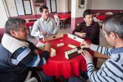 Local turkish men playing very table game Okey, or rummikub, in. Antalya,Turkey -aprill 22, 2012: Local turkish men playing very popular local table game Okey Royalty Free Stock Images
