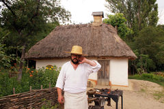 Local Ukrainian man near traditional rural house in Museum Pirog Royalty Free Stock Photos
