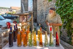 Local vendor selling homemade wine and liquor in Croatia, senior business