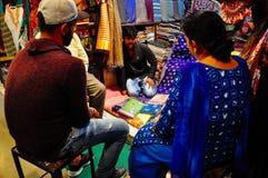 A vendor sells silk in Varanasi, India. A local vendor sells silk scarfs in Varanasi, India royalty free stock photography