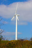 A local wind turbine with its 3 vanes stands idle on a bright spring afternoon in Conlig in Northern Ireland Royalty Free Stock Photography