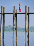 Local woman with basket on her head walking on U Bein bridge, Am Stock Photos