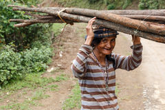 Local Woman Carrying Goods on Head in Chin State, Myanmar. FALAM, MYANMAR - JUNE 17 2015: Local woman carries wood on her head in the recently opened to royalty free stock photo
