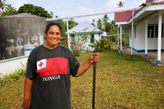 Local woman cleaning church yard, Ofu island, Tonga Royalty Free Stock Photo