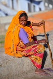 Local woman in colorful sari sitting on a stone wall, Jaipur, In Royalty Free Stock Photo