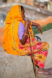 Local woman in colorful sari sitting on a stone wall, Jaipur, In Stock Photos