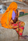 Local woman in colorful sari sitting on a stone wall, Jaipur, In Stock Image
