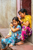 Local woman grooming for lice on her daughter`s head in Fatehpur. Sikri, Uttar Pradesh, India. The city was founded in 1569 by the Mughal Emperor Akbar, and royalty free stock images