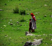 Local woman with kid in Kashmir. Walking home somewhere in Sonamarg stock images