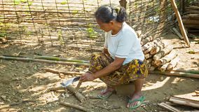 Local woman makes a wooden peg with a machete Stock Photos
