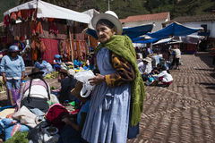 Local woman in a market in the city of Pisac, in the Sacred Valley. Pisac, Peru - December, 2013: Local woman in a market in the city of Pisac, in the Sacred Stock Photos