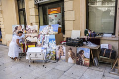 Local woman offers paintings to tourists Stock Images
