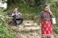 Local woman and trekker resting on mountain path. Stock Image