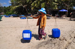 A local woman in Vietnam is taking fresh water to her fishing boat for a long day fishing in among the sea Royalty Free Stock Photo