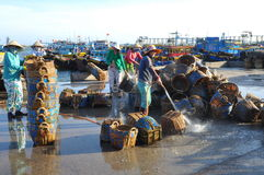 Local women are cleaning their baskets which were used for transporting fishes from the boat to the truck Royalty Free Stock Photos