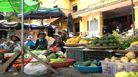 Local women stall holders and people on the daytime streets at Hoi An Market, Vietnam stock footage