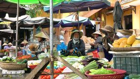 Local women stall holders and people on the daytime streets at Hoi An Market, Vietnam. LOCAL WOMEN SELLING FOOD VEGETABLES AT HOI AN MARKET, VIETNAM – 6 stock video footage