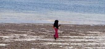 Local  women in Zanzibar, Tanzania. Woman walking on the beach Zanzibar island, Tanzania Royalty Free Stock Images