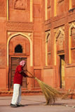 Local worker sweeping courtyard of Jahangiri Mahal in Agra Fort, Stock Photography