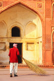 Local worker sweeping courtyard of Jahangiri Mahal in Agra Fort, Royalty Free Stock Photo