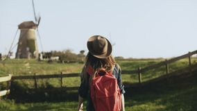 Local young girl walks around old windmill farm. Cowgirl in hat with long hair and red backpack wanders thoughtfully. 4K. Lady enjoying amazing pastoral stock video