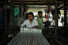 local young woman using a traditional loom with her kids stock photography
