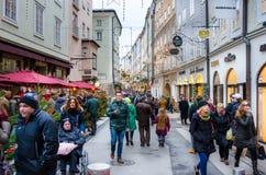 Locali e turisti che camminano lungo una via allineata con i negozi ed i monumenti storici Immagini Stock Libere da Diritti