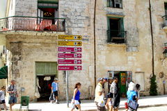 Locali e turisti che camminano sulla via con i segni Fotografia Stock