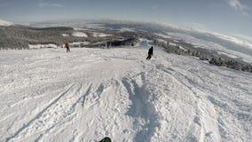 località di soggiorno di corsa con gli sci dell'alta montagna 4K: lo sciatore scende la collina video d archivio