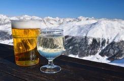 Località di soggiorno di corsa con gli sci. Vetri con birra e vino bianco. fotografie stock libere da diritti