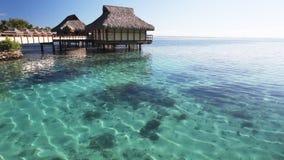 Località di soggiorno tropicale stupefacente con le capanne sopra acqua blu stock footage
