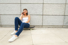 Localización de la chica joven en el monopatín en la ciudad con el móvil Imagen de archivo libre de regalías